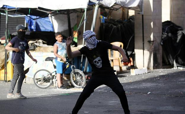 A Palestinian throws a stone at Israeli soldiers in Hebron./efe