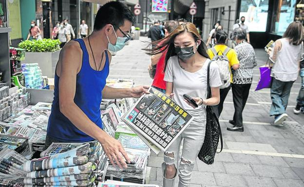 A young woman buys a copy of the 'Apple Daily' from a Hong Kong newsstand.  / efe