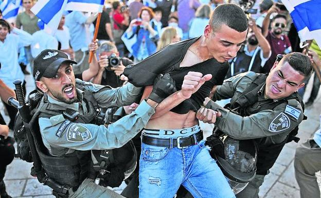 Two agents arrest a Palestinian amid the march of Jewish ultranationalists in Jerusalem. / AFP
